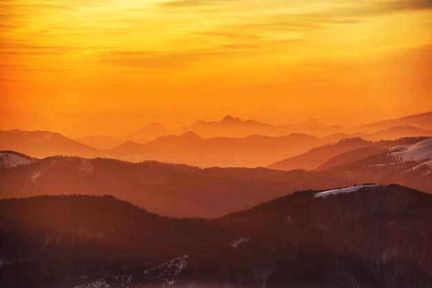 劇的な冬の山々に沈む夕日