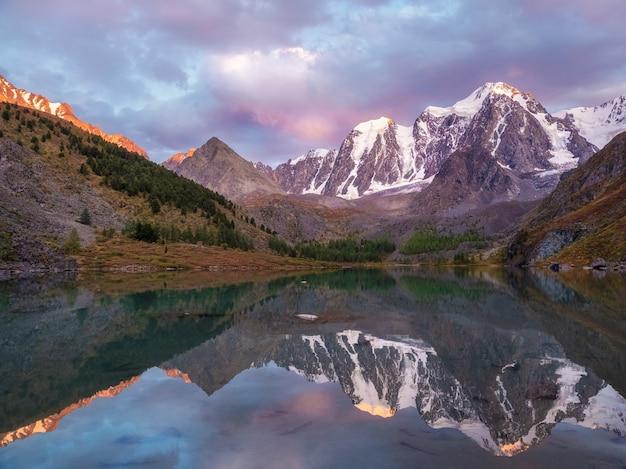 マゼンタ調の夕焼け。山の高い氷河湖。高地の雪に覆われた山の谷に湖がある雰囲気のある紫色の風景。アルタイ山脈。