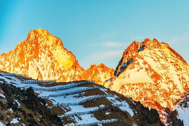 눈으로 덮여 산에서 일몰입니다.