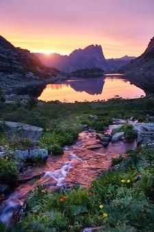 Закат в горах у реки. солнечный свет отражается на горных вершинах. золотой свет неба отражается в горной реке. ергаки. шум, нет фокуса