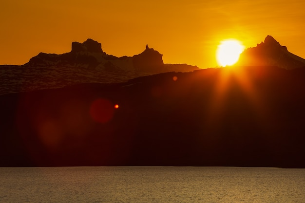 Закат в скалистых горах и на берегу озера красно-оранжевое солнце садится за силуэт скалы горного хребта