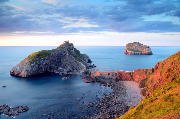 Закат в сан-хуан-де-гастелугаче на фоне острова акеткс и спокойного моря