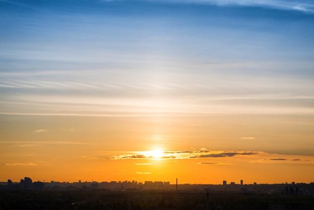 大都会の夕日。建物、太陽、劇的なオレンジ色の空