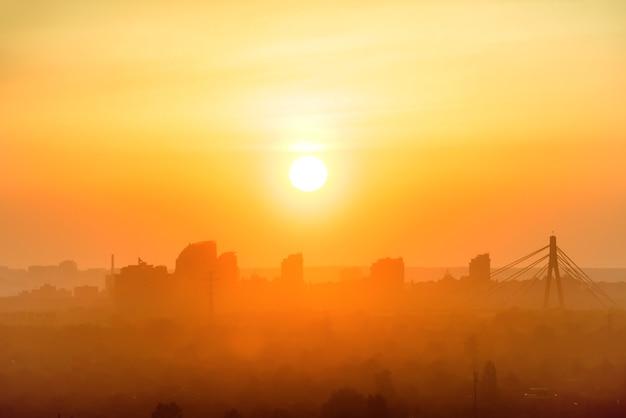 도시에서 일몰입니다. 하늘에 오렌지 태양이 있는 스카이라인