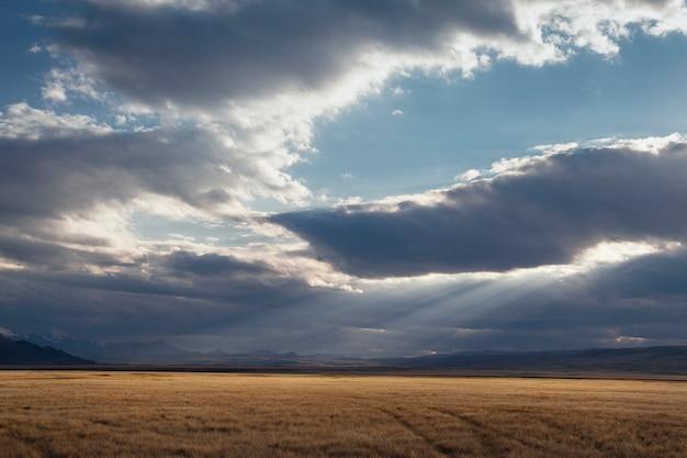 사막의 일몰, 태양 광선 구름을 통해 빛납니다. 알타이의 ukok 고원. 멋진 추운 풍경. 주위에 아무도