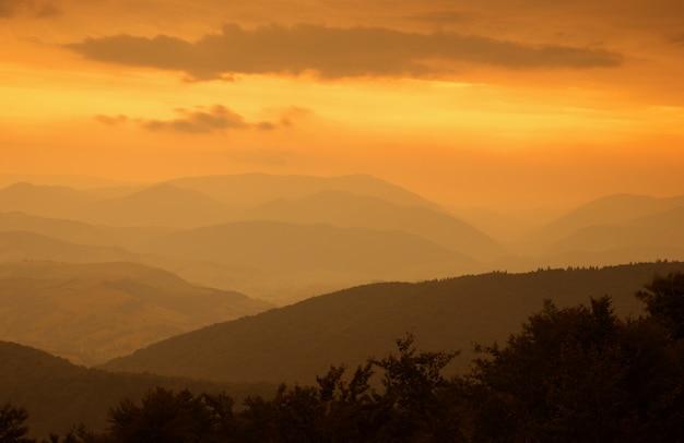 霧の秋の山の夕日