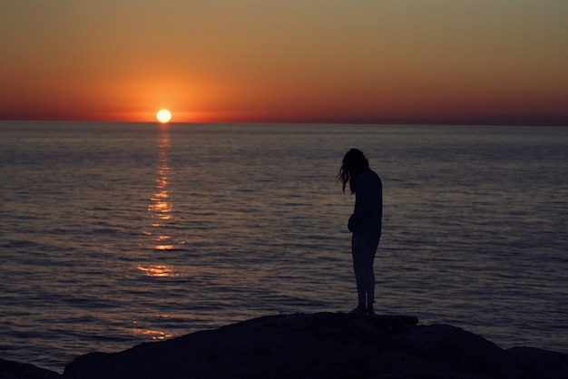 海沿いの山々に沈む夕日とビーチの女性のシルエット