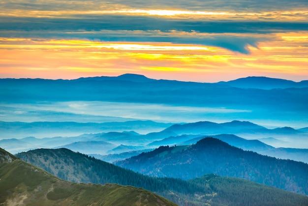 산에서 일몰입니다. 푸른 언덕 위의 극적인 다채로운 구름