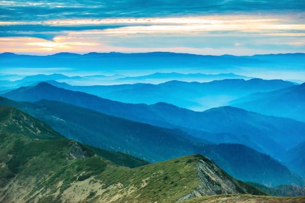 산에서 일몰입니다. 푸른 언덕이 있는 극적인 다채로운 하늘