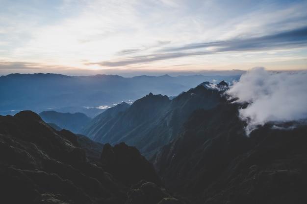 山に沈む夕日。ファンシーパン山の高い山から夕方の雲までの暗い夜景。ベトナム渓谷の夕日