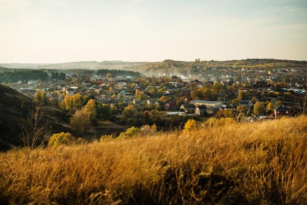 小さな村を眺めながら秋の山に沈む夕日。黄色い草と澄んだ空。背景の小さな家。山での平和、リラクゼーション、生活。ささいなことの幸せ