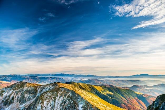 山に沈む夕日。丘、青い空と雲のある風景
