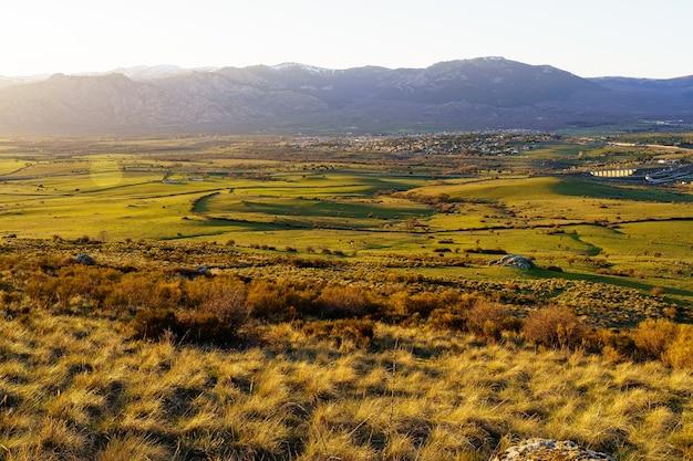 山腹に小さな村、田舎に牛や農場がある山に沈む夕日。ナバセラダマドリード。スペイン。