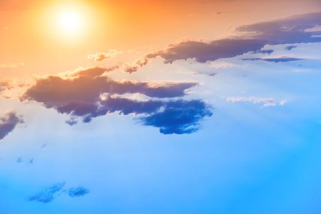 Закат в оранжевом небе с большим солнцем и синим облаком