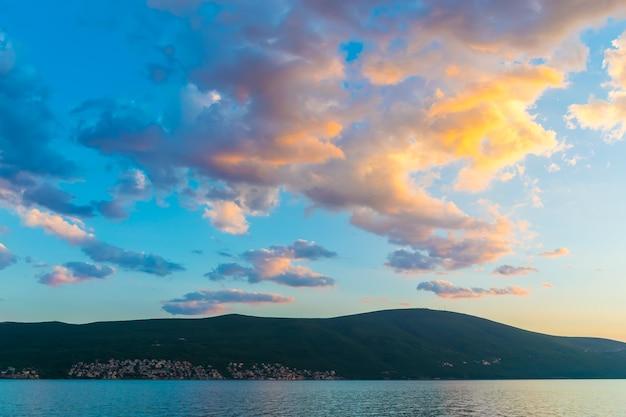 Закат в небе черногории над высокими горами.