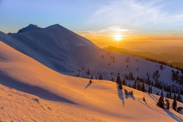 Закат в зимних горах, оранжевое небо в заснеженных карпатах