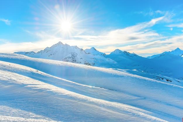 雪に覆われた冬の山々に沈む夕日。青い空に輝く太陽