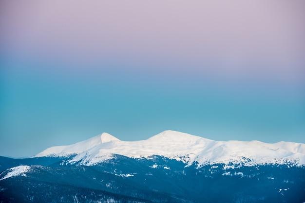 雪に覆われた冬の山々に沈む夕日。ウクライナ、ホヴェールラ、ペトロス