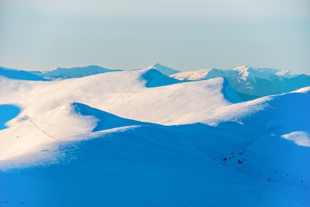 雪に覆われた冬の山々に沈む夕日。