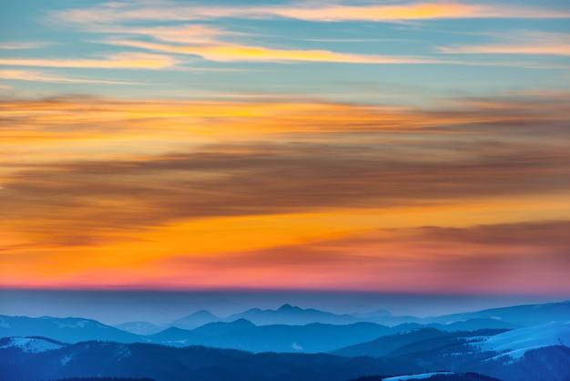 雪に覆われた冬の山々の夕日