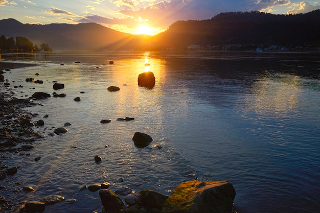 Sunset on the lake on a background of stones in a clear summer day
