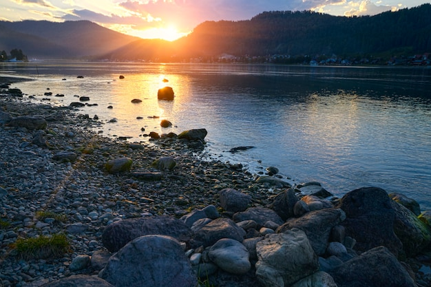 Sunset on the lake on a background of stones in a clear summer day.