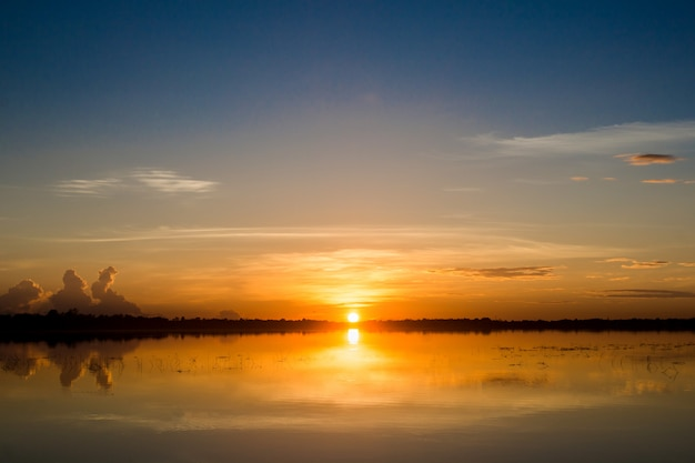 Sunset in the lake. beautiful sunset behind the clouds above the over lake landscape background.