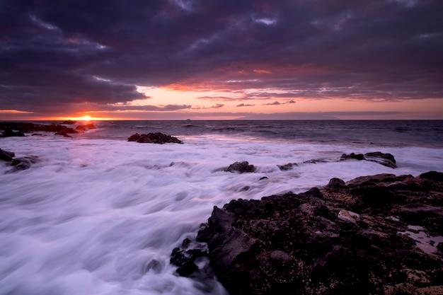 海の海と波を背景にしたビーチの夕日の風景-太陽と雲の劇的な空-夕暮れの光と地平線