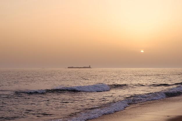 백그라운드에서 성이 있는 해변과 바다의 일몰 풍경