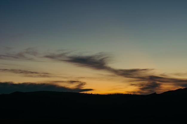 谷の日没の風景。明確な地平線上の植物や木のシルエット。絵のようです。魔法の空。
