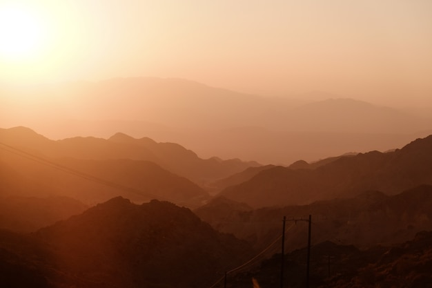 Sunset over layer of mountain ranges.