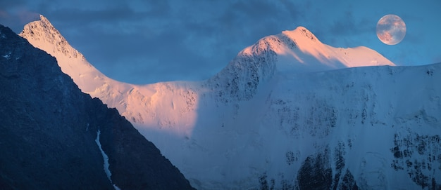 산에서 일몰 빛, 봉우리 위에 보름달. 파노라마, 벨 루하 산, 알타이.