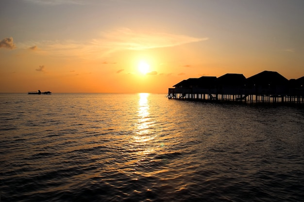 Sunset on maldives island with water villa resort and reflection of sunlight on sea