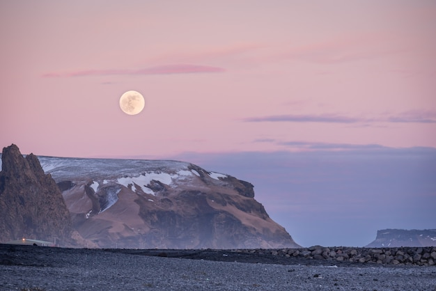 Sunset and moon rise over mountains and vik's black sand beach in iceland at dusk