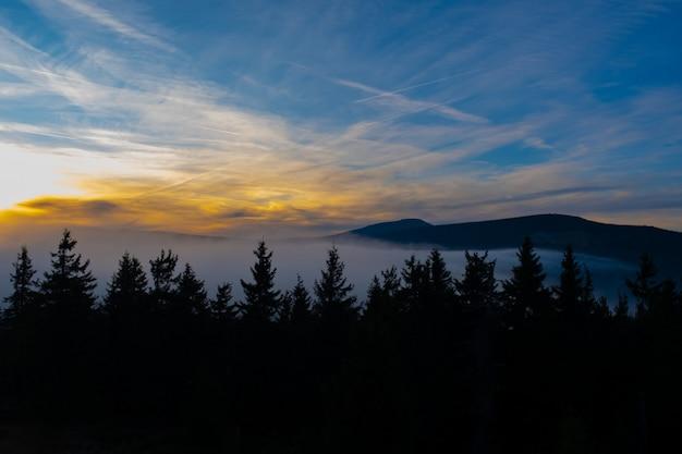 Sunset mountain sky blue colorful autumn sun light yellow orange clouds tree smoke fog haze