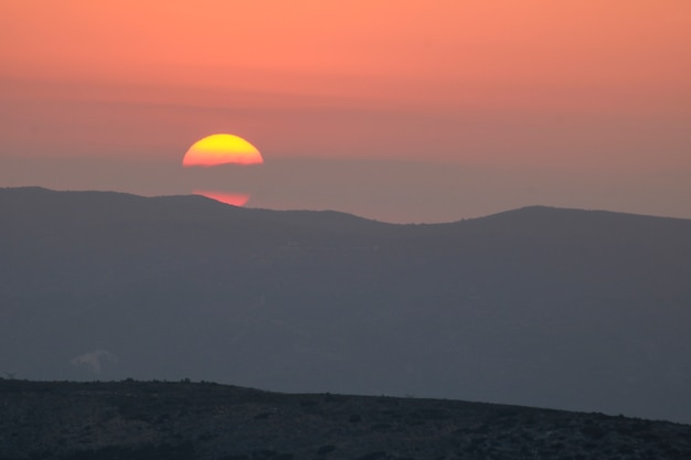 Sunset on the mountain, sun setting behind the mountain.