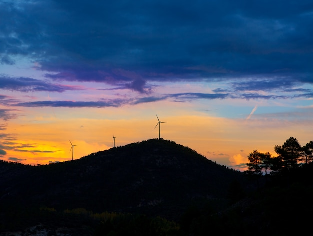 Sunset mountain with electric windmills