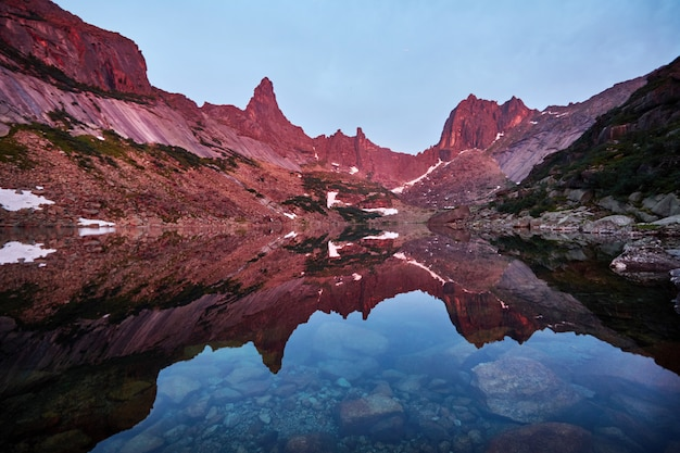 Sunset in mountains near lake. sunlight reflected on mountain tops
