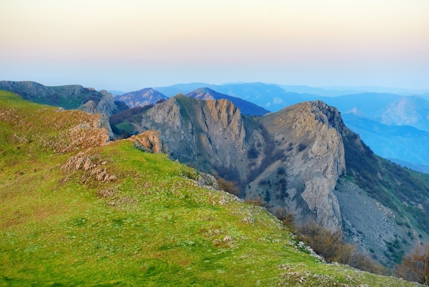 Sunset in the mountains with rocks and green grass