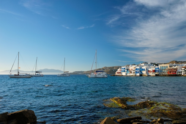 Sunset in mykonos greece with cruise ship and yachts in the harbor