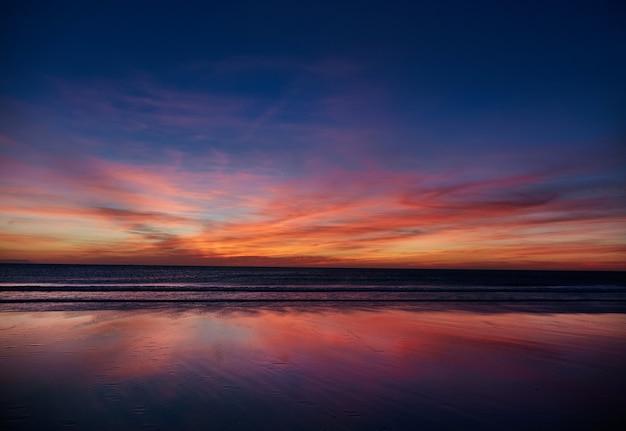 Пляж на закате в испании в андалусии. атлантический океан волны фон яркий волшебный лето закат небо