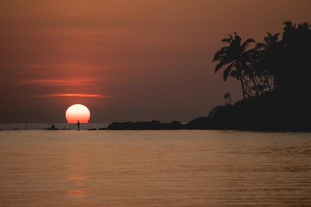 Sunset ocean view. sun above the sea on orange sky.