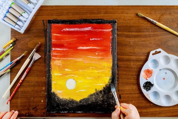 サンセット油絵、ブラシ、パレット。キャンバス上のアート。