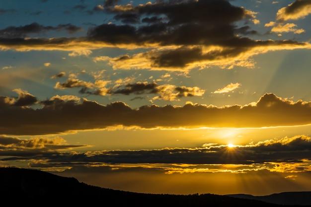 구름과 태양 광선이 산에서 나오는 날의 일몰.