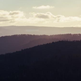 かすんでいる山に沈む夕日。美しい夕日で山の地平線。