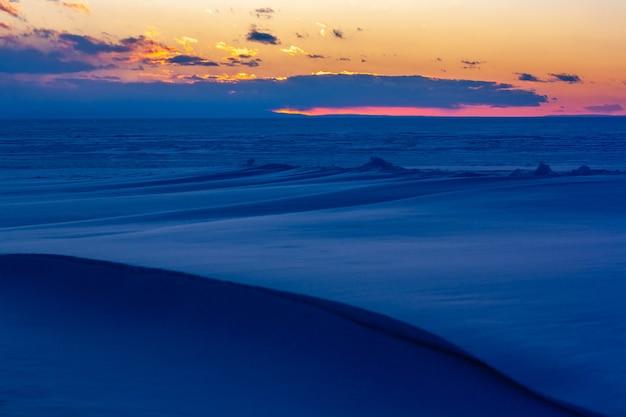 Закат на байкале зимой. лед под снегом. красное солнце за облаками. голубой снег. по горизонтали.