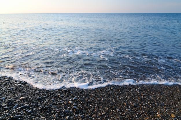 Закат на берегу моря, скалистом пляже и голубом небе. небольшие холмы, покрытые зелеными растениями на заднем плане