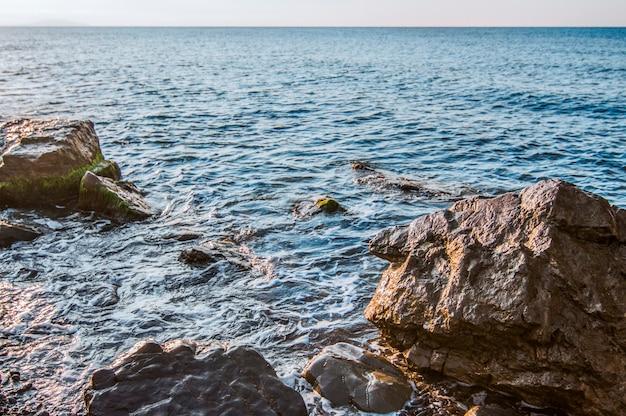 海岸、岩の多いビーチ、青い空に沈む夕日。