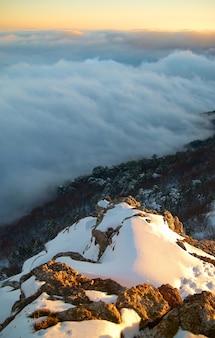 雪に覆われた山々に沈む夕日。