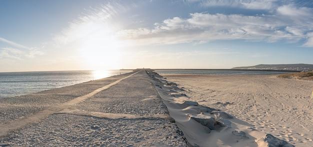 風の強い日、海へのアスファルト道路に沈む夕日
